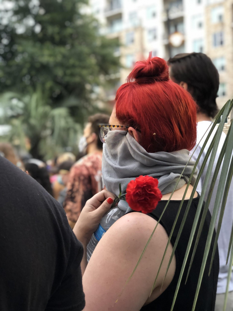 A woman holds a rose at the vigil Tuesday night.